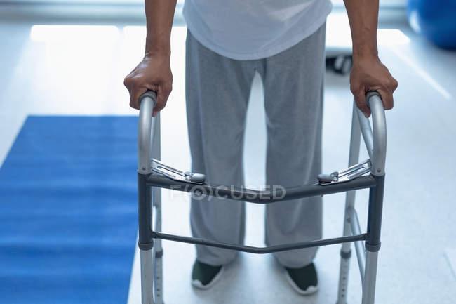 Нижняя часть пациента мужского пола, идущего с ходячим в палате больницы — стоковое фото