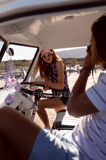 Вид сбоку на молодого кавказца, фотографирующего женщину на переднем сиденье фургона на пляже — стоковое фото
