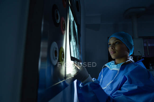 Side view of young mixed race female surgeon holding x-ray against light box while examining it in operation theater at hospital. Surgeon wears surgical gown, cap, and mask. — Stock Photo