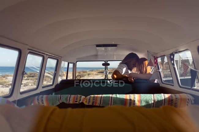 Заднього виду романтичної молоді кавказька пара цілуватися один з одним в передній сидіння кемпер Ван на пляжі — стокове фото
