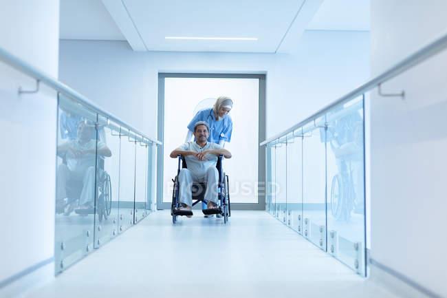 Frontansicht einer Ärztin im Hijab, die einen älteren Patienten im Rollstuhl im Krankenhausflur schubst. — Stockfoto