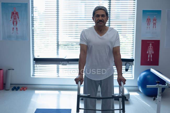 Пациент смешанной расы, идущий с ходячим в палате больницы — стоковое фото