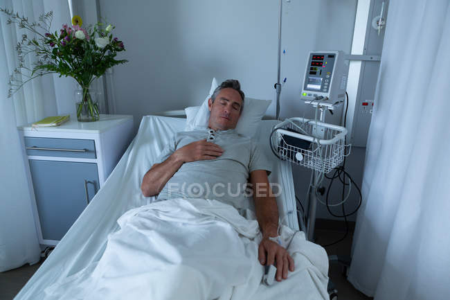 High angle view of mature Caucasian male patient sleeping in bed with right hand on his chest in the ward in hospital — Stock Photo