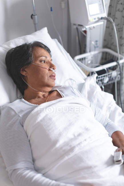 High angle view of thoughtful mixed-race female patient relaxing in bed in the ward at hospital — Stock Photo