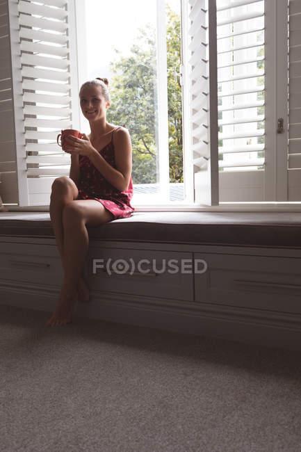 Вид спереди красивой кавказской женщины с кружкой кофе, сидящей на подоконнике в спальне дома — стоковое фото