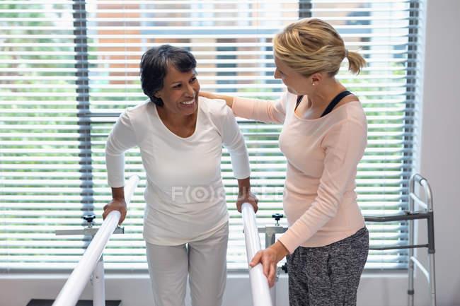 Vista frontal de fisioterapeuta femenina caucásica ayudando a la paciente de raza mixta a caminar con barras paralelas en el hospital - foto de stock
