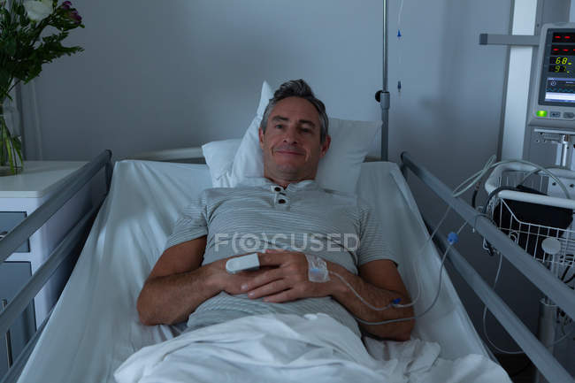 Portrait of Caucasian male patient relaxing in the ward while lying in bed in hospital — Stock Photo