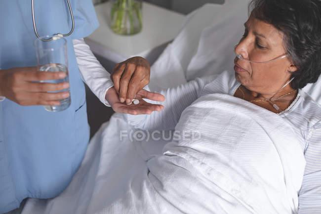 Primer plano de la doctora de raza mixta que da medicina a una paciente de raza mixta madura en la sala del hospital - foto de stock