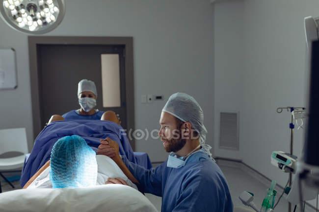 Vorderseite der kaukasischen Chirurgin untersucht schwangere Frau während der Entbindung, während kaukasischer Mann ihre Hand im Operationssaal im Krankenhaus hält. — Stockfoto