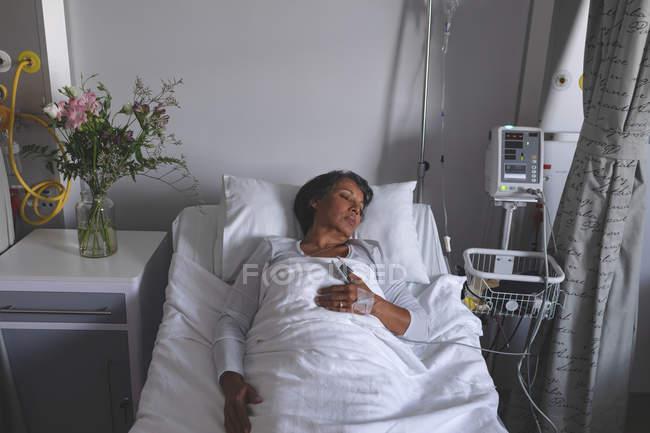 Vista de ángulo alto de la paciente de raza mixta que duerme en la cama con una mano en el estómago en la sala del hospital. Flores están de pie en el armario al lado de la cama . - foto de stock