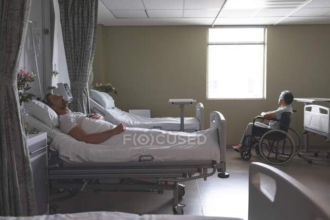Side view of mature Caucasian male patient sleeping in bed while senior mixed-race male patient is sitting in wheelchair next to the window in the ward at hospital — Stock Photo
