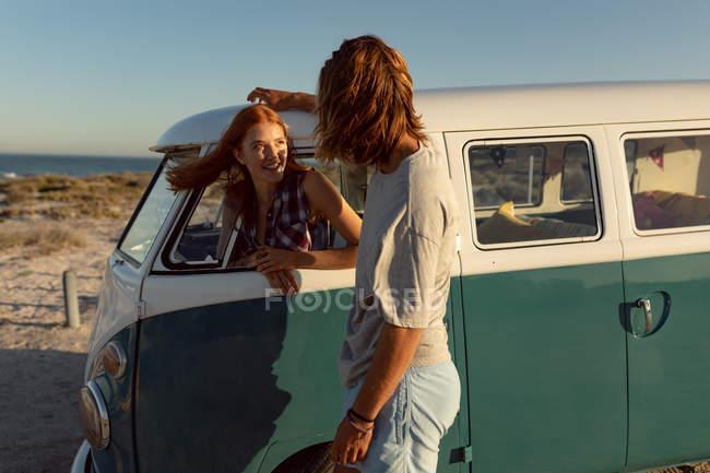Вид збоку щаслива кавказька жінка розмовляв з людиною в кемпер Ван на пляжі — стокове фото