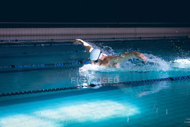 Вид збоку чоловічого Кавказького плавця тримає окуляри на білій кришкою, стоячи в басейні — стокове фото