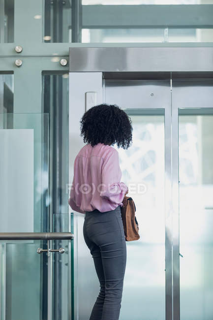 Rear view of African american female executive waiting for the lift in modern office — Stock Photo
