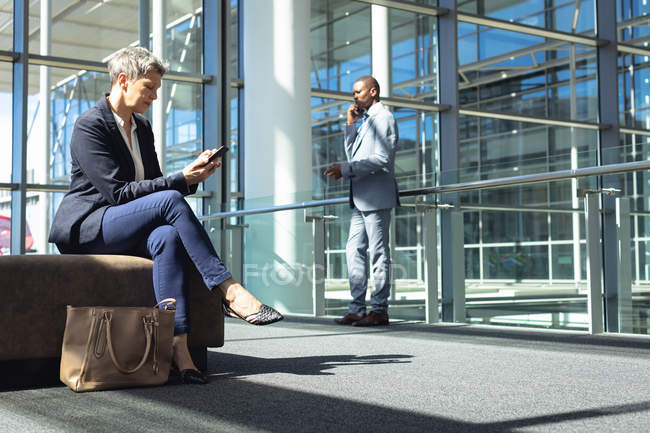 Side view of Caucasian female executive looking at her mobile phone while sitting in a chair in modern office. Behind her, African american businessman speaking on mobile phone. — Stock Photo