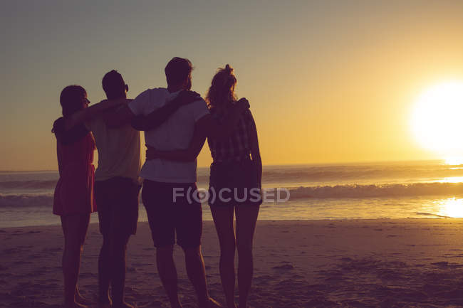 Rear view of diverse friends standing with arms around on the beach during sunset — Stock Photo