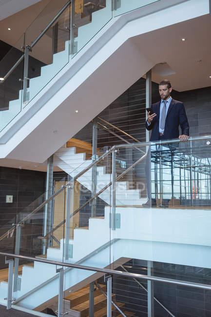 Вид спереди бизнесмена с мобильным телефоном у перил в современном офисном здании — стоковое фото