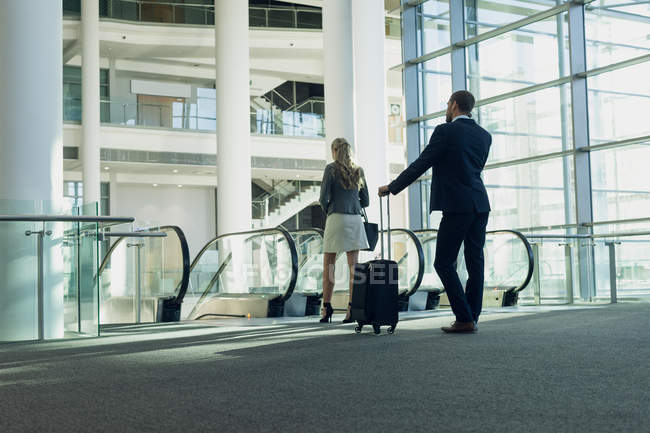Rear view of business people standing near escalator in the modern office building — Stock Photo