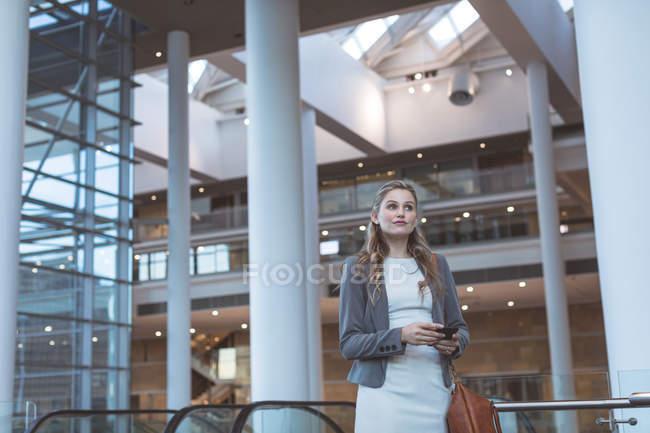 Vista frontale della donna d'affari che cammina vicino alla scala mobile in un moderno edificio per uffici — Foto stock