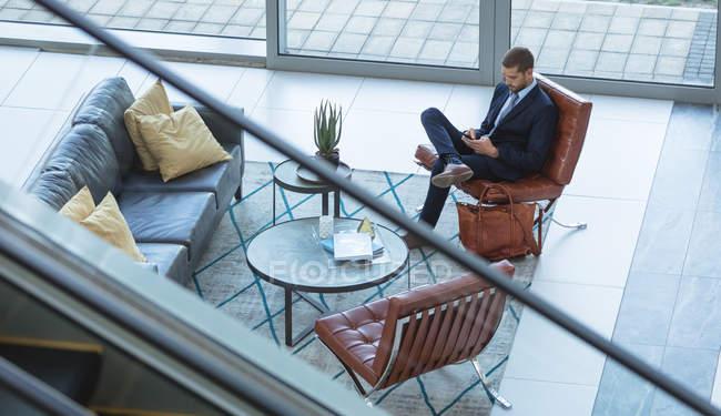 Vue grand angle de l'homme d'affaires utilisant le téléphone portable dans le hall au bureau moderne — Photo de stock