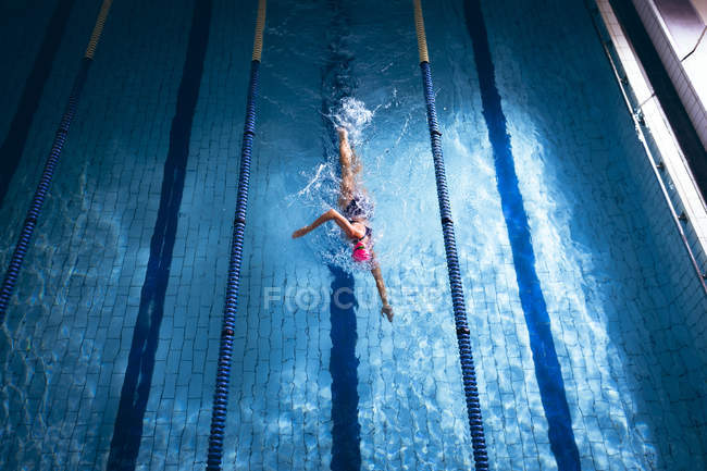 High angle view of a Caucasian woman wearing a pink swimming cap and goggles doing a freestyle stroke in a swimming pool — Stock Photo