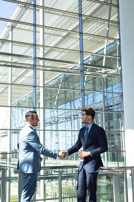 Vue latérale de cadres masculins caucasiens serrant la main tout en se tenant dans le bureau moderne — Photo de stock