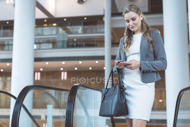 Вид спереди красивой бизнесвумен с мобильным телефоном у эскалатора в современном офисном здании — стоковое фото