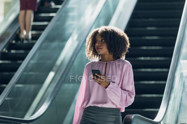 Фронтальный вид африканской бизнесвумен, смотрящей на мобильный телефон во время использования эскалаторов в современном офисе — стоковое фото