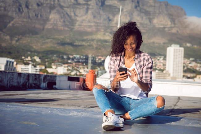 Vista frontale di una giovane donna afro-americana che indossa una giacca a quadri sorridente mentre è seduta e usa un telefono cellulare su un tetto con luce solare — Foto stock