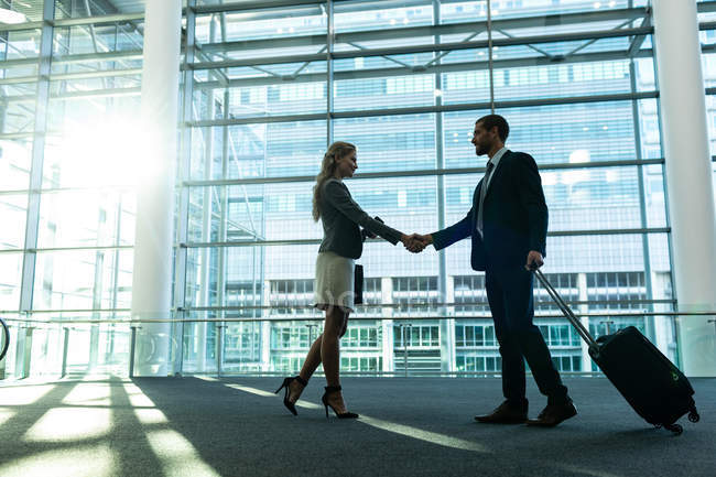 Side view of business people shaking hands in the modern office building — Stock Photo