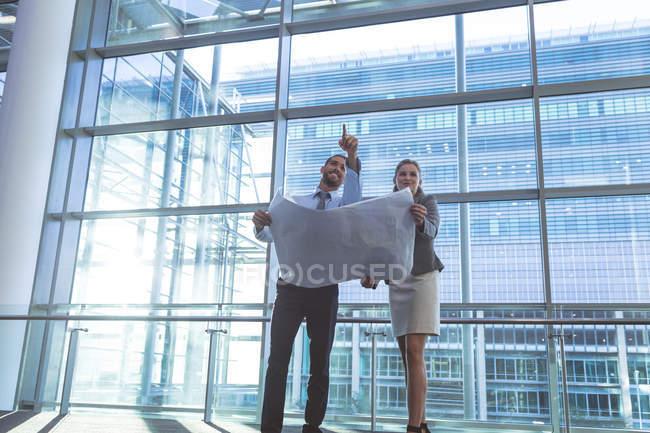 Vista a basso angolo degli uomini d'affari che discutono sul progetto in un moderno edificio per uffici — Foto stock