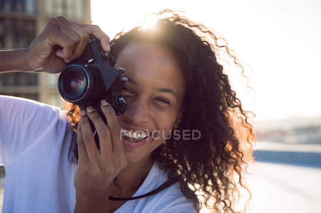 Vista frontal de uma jovem afro-americana sorrindo enquanto segurava uma câmera e estava em um telhado com vista para um prédio e para a luz do sol — Fotografia de Stock