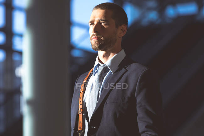 Close-up of businessman with office bag looking away in a modern office building — Stock Photo