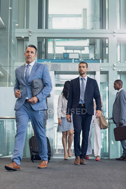 Vue de face des cadres masculins caucasiens marchant dans le couloir dans le bureau moderne — Photo de stock