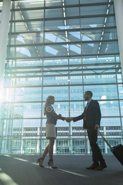 Vue à angle bas de gens d'affaires serrant la main dans l'immeuble de bureaux moderne — Photo de stock