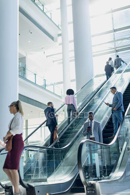 Вид збоку різних ділових людей, що використовують ескалатори в сучасному офісі — стокове фото