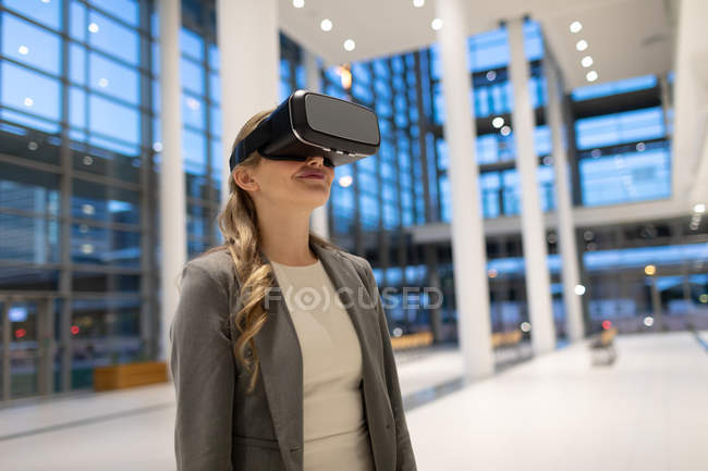 Front view of businesswoman using virtual reality headset in the lobby at modern office — Stock Photo