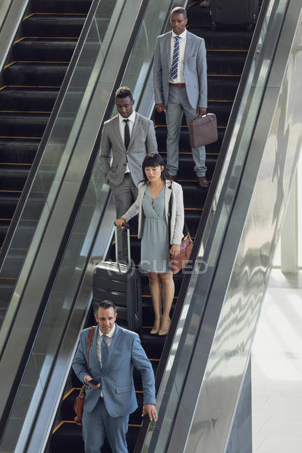 Front view of diverse business people using escalators in modern office — Stock Photo