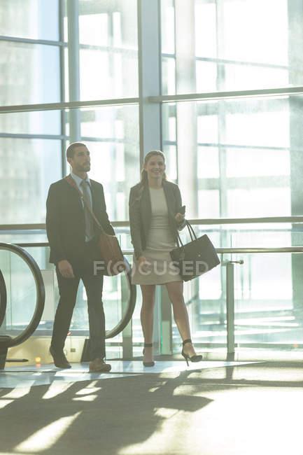 Вид деловых людей, сходившихся у эскалатора в современном офисном здании — стоковое фото