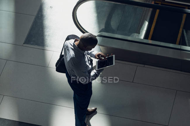 High angle view of African american businessman looking at digital tablet in modern office — Stock Photo