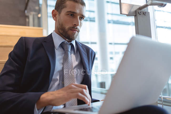 Primo piano di un uomo d'affari che lavora su un computer portatile su scale in un moderno edificio per uffici — Foto stock