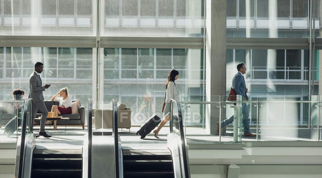 Side view of diverse business people walking in modern office — Stock Photo