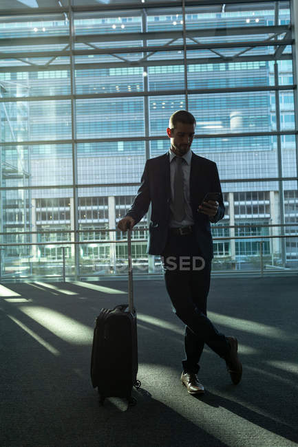 Front view of businessman with trolley bag using mobile phone in the modern office building — Stock Photo
