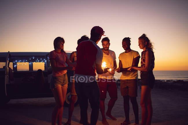 Vista frontale di gruppo di diversi amici illuminazione scintille vicino cameraman durante il tramonto — Foto stock