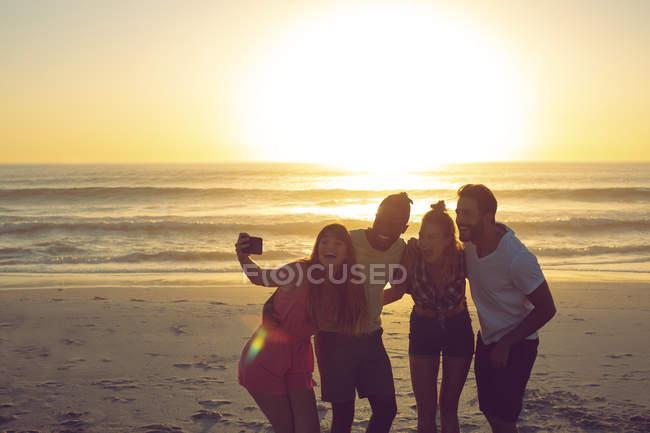Vue de face du groupe d'amis divers prenant selfie avec téléphone portable à la plage pendant le coucher du soleil — Photo de stock