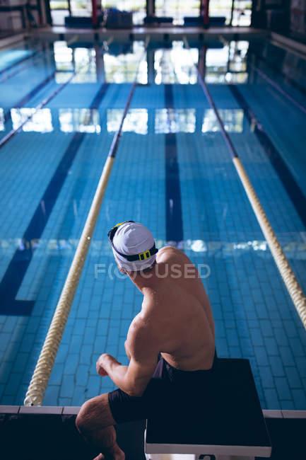 Vista traseira de um nadador caucasiano sentado numa prancha de mergulho junto à piscina — Fotografia de Stock