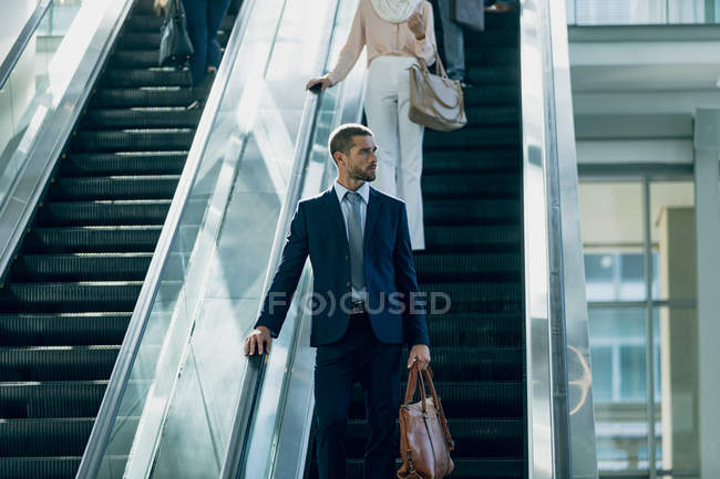 Front view of Caucasian businessman using escalators in modern office — Stock Photo