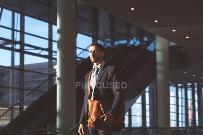 Vue latérale de l'homme d'affaires réfléchi avec sac de bureau regardant loin dans un immeuble de bureaux moderne — Photo de stock