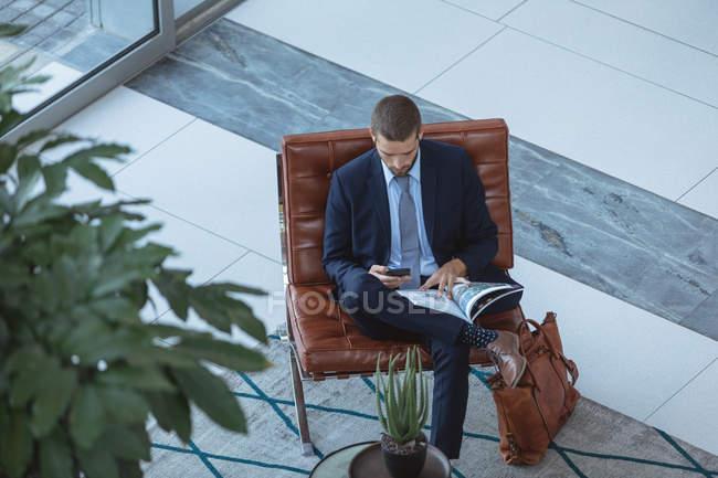 Vista ad alto angolo dell'uomo d'affari che utilizza il telefono cellulare nella hall dell'ufficio moderno — Foto stock
