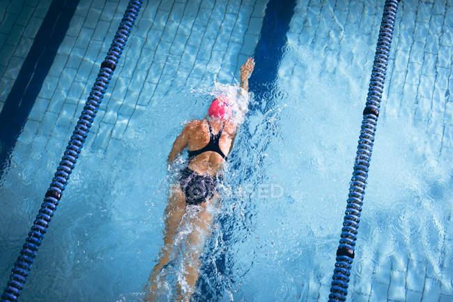 Vue en angle élevé d'une femme caucasienne portant un bonnet de bain rose et des lunettes faisant un coup de style libre dans une piscine — Photo de stock